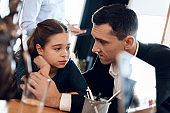 Young father calms daughter while sitting at desk in office of family lawyer.