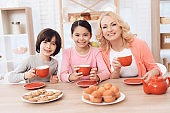 Elderly woman and cheerful grandson and granddaughter drink tea from red mugs in kitchen.