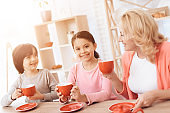 Elderly woman and happy grandson and granddaughter drink tea from red mugs in kitchen.