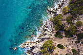 aerial top view of a clear ocean with rocky coast
