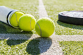 paddle tennis racket and tube with balls on turf