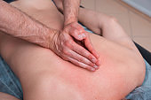 Male Physical therapist is pressing on one mans back with both hands together