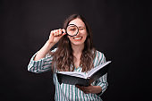 Smiling girl looking through a magnifying glass is holding a journal