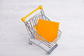 yellow trolley with orange paper for check list , shopping online concept
