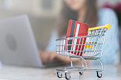 photo of woman making online shopping with troley background.
