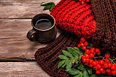 Autumn good mood concept. Warm knitted scarf, hot drink, ripe rowan berries. Wooden boards background