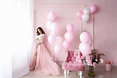 Elegant woman in a bride dress on a background of pink inflatable balloons