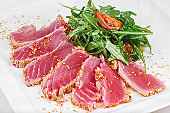Sliced tuna fish grill with sesame seeds, tomatoes and arugula