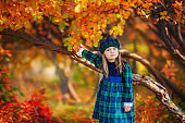Baby girl dressed in the French style on the background of bright yellow leaves in autumn forest