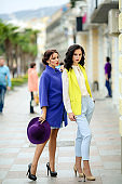 Two women models in fashion clothes on a summer avenue