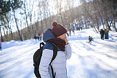 An adult in warm winter clothes has fun and laughs outdoors during a winter walk