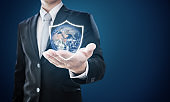 Businessman holding globe with shield icons. Protect the world and environmental conservation. Element of this image are furnished by NASA