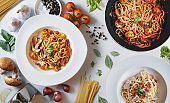 Italian food, Pasta Bolognese, tomatoes sauce, and Carbonara with fresh ingredients, on black table