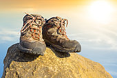 closeup pair of touristic boot stay on a stone at the sunset, outdoor travel background