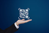 Businessman holding QR code on hand. QR code scanning payment and verification technology