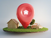 House symbol with location pin icon on earth and green grass in real estate sale or property investment concept.