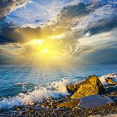 stony sea beach at the sunset