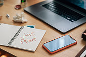 Just Start - a Motivational Message Written in a Businesswoman's Notebook Placed on the Desk alongside a Mobile Phone