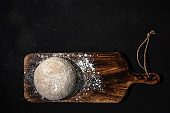 Fresh raw dough for bread or pizza on a rustic wooden background with dusting of flour. Top view.