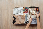 Hands of an Unrecognizable Woman Traveler Packing her Suitcase