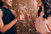 Two Happy Women Celebrating New Year's Eve With a Champagne Toast Under Confetti