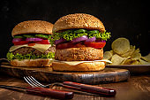 Two fresh tasty burgers on wooden rustic table. Food background.