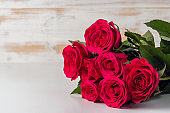 Bouquet of red roses on wooden table. Greeting card for Valentines Day, Womens Day. Holiday concept.