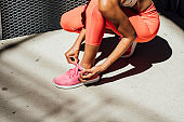 Unrecognizable Fit African Sportswoman in Red Sportswear Tying Shoelaces on Sneakers During a City Run