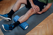 Foam Roller Massage after a Home Workout: a Man in Sportswear Relaxing his Muscles after Exercising in the Living Room
