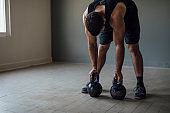 Handsome Sportsman in a Sleeveless Shirt Exercising with Kettlebell Weights
