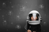 a child in an astronaut's helmet dreams of Christmas and presents