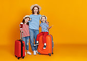 happy journey! family of travelers mother and children with suitcases tickets and passports on yellow background