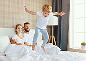 happy family mother, father and child  laughing, playing and jumping in bed
