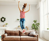 Happy woman listening to music and jumping and dancing on couch at home
