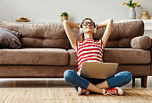 Pleased young woman in headphones with laptop listening to music while relaxing on sofa at home
