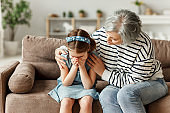 Grandmother supporting crying granddaughter at home