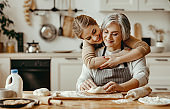 happy family grandmother  old mother mother-in-law and daughter-in-law daughter cook in kitchen, knead dough, bake cookies