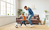 Father and son playing football at home