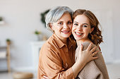 Happy senior woman with daughter hugging at home