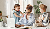 Little children distracting dedicated young woman working on laptop at home