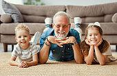 Happy grandfather lying on floor with grandchildren