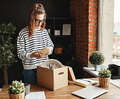 Happy woman newcomer unpacking carton box at table in new workplace in loft office