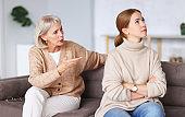 Upset women sitting on sofa after quarrel