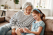 Grandmother and granddaughter using smartphone on sofa