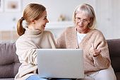 Cheerful mother and daughter using laptop together