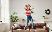 Happy woman listening to music and dancing on couch at home