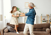Grandfather dancing with granddaughter at home