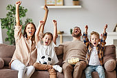 family of fans watching a football match and celebrating goal on TV at home