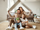 concept housing  young family. mother father and children under fake roof in  new home
