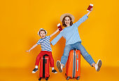 happy journey! family of travelers mother and child  with suitcases tickets and passports on yellow background